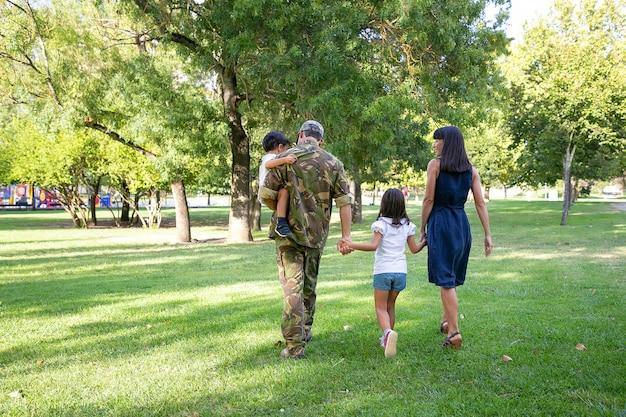 Achteraanzicht van gelukkige familie die samen op weide in park loopt. vader draagt camouflage-uniform, houdt zoon vast en geniet van weekend met vrouw en kinderen. familiereünie en het concept van thuiskomst