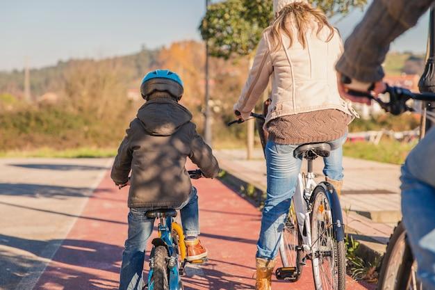Achteraanzicht van gelukkige familie met een kind fietsen door de natuur op een zonnige winterdag