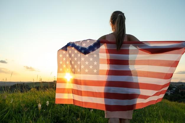 Achteraanzicht van gelukkige jonge vrouw poseren met de nationale vlag van de vs die buiten staat bij zonsondergang. positief meisje dat de onafhankelijkheidsdag van de verenigde staten viert. internationale dag van democratie concept.