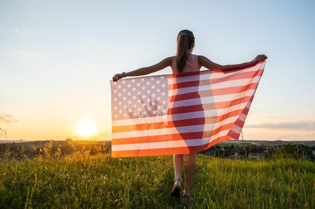 Achteraanzicht van gelukkige jonge vrouw poseren met de nationale vlag van de vs die buiten staat bij zonsondergang. positieve vrouw die de onafhankelijkheidsdag van de verenigde staten viert. internationale dag van democratie concept.