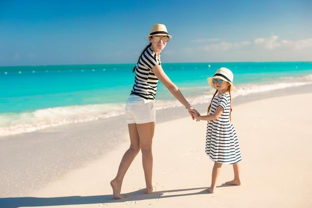 Achteraanzicht van gelukkige moeder en kleine dochter op caribisch strand