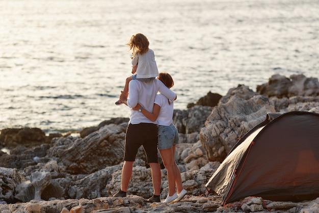 Achteraanzicht van gelukkige ouders met kleine dochter, zittend op de nek.