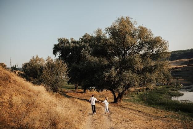 Achteraanzicht van gelukkige paar is hand in hand, loopt en heeft plezier in het park. plezier, emoties.