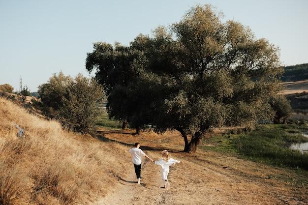 Achteraanzicht van gelukkige paar is hand in hand, loopt en heeft plezier in het park.