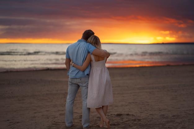 Achteraanzicht van gelukkige paar knuffelen op het strand bij zonsondergang