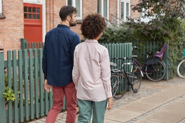 Achteraanzicht van gemengd ras paar hand in hand, ga naar huis na een buitenwandeling, ga fietsen, draag stijlvolle outfit