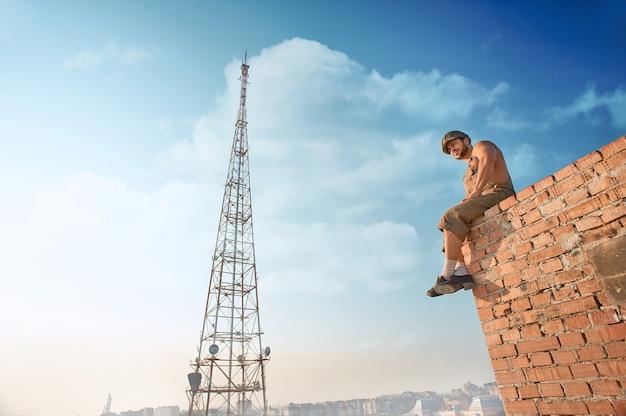 Achteraanzicht van gespierde bouwer in werkkleding staande op bakstenen muur op hoog. man hand in hand in zakken en naar beneden te kijken. extreem in warme zomerdag. blauwe lucht en hoge tv-toren op de achtergrond.