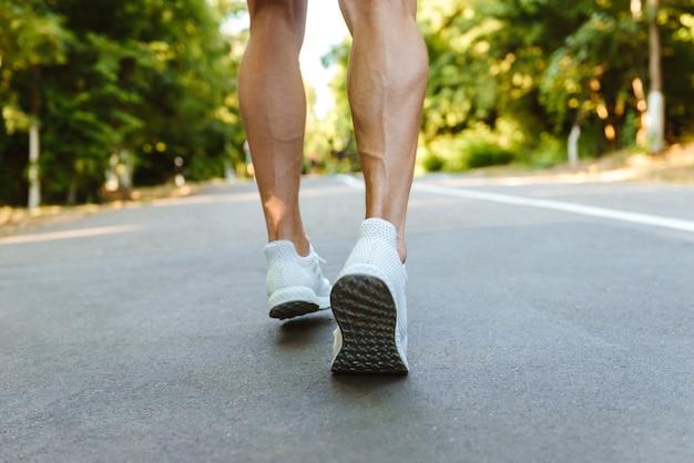 Achteraanzicht van gespierde sportman benen lopen