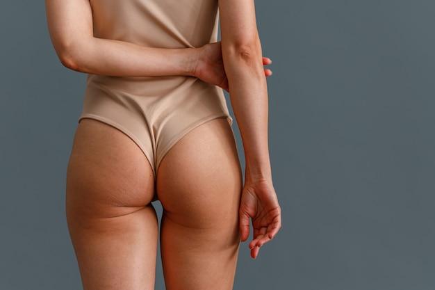 Achteraanzicht van getinte billen van vrouw in beige bodysuit staande geïsoleerd over grijze studio achtergrond