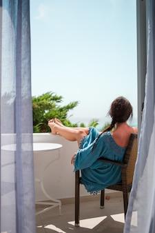 Achteraanzicht van geweldige vrouw geniet van uitzicht op zee vanaf haar balkon