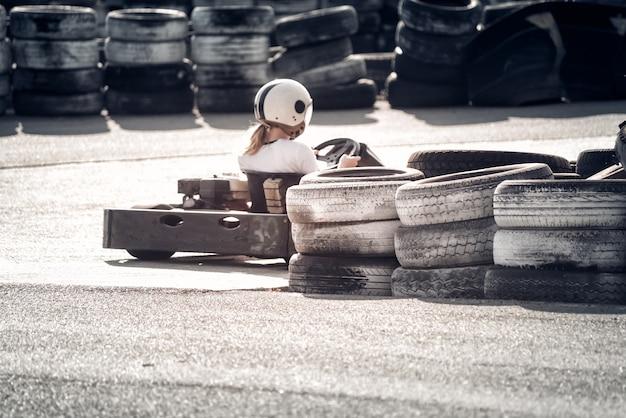 Achteraanzicht van go-kart-coureur die op het circuit rijdt