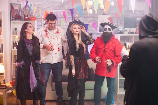 Achteraanzicht van grim reaper die foto's maakt van vampiervrouw en haar vrienden op halloween-feest.