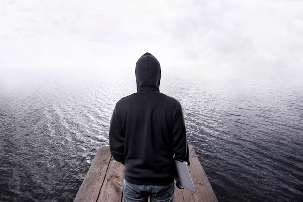 Achteraanzicht van hacker in de motorkap, met laptop in de hand, op houten pier die in het water en mist gaat, concept van programmeerproblemen