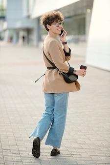 Achteraanzicht van hedendaagse jonge zakenvrouw met drankje en handtas die smartphone op het gehoor vasthoudt terwijl ze zich omdraait en vooruitkijkt