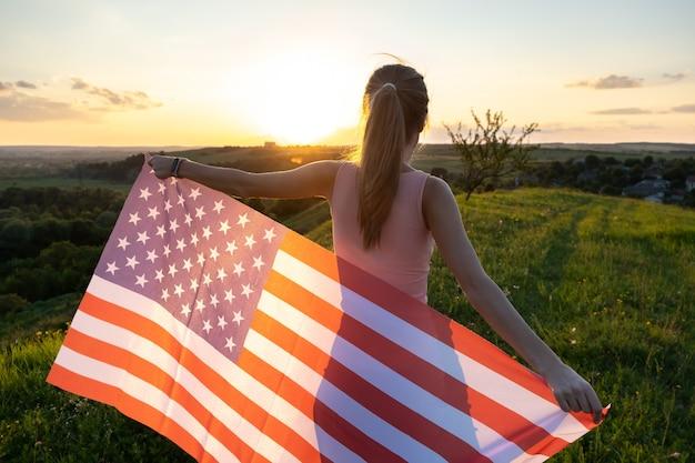 Achteraanzicht van het gelukkige jonge vrouw stellen met de nationale vlag van de vs die zich buiten bij zonsondergang bevindt.