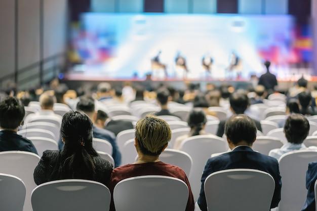 Achteraanzicht van het luisteren van audience luidsprekers op het podium in de conferentiezaal