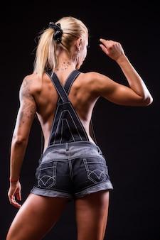 Achteraanzicht van het portret van een mooie atletische vrouw op donker