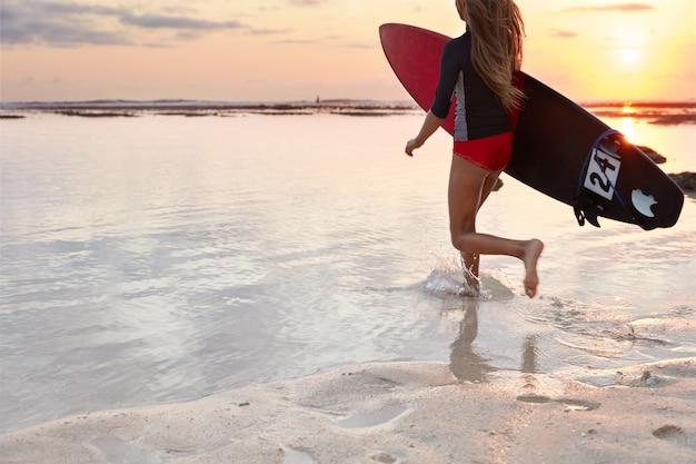 Achteraanzicht van het runnen van meisje surfer in zwembroek, draagt bord onder de arm, klaar om gigantische golf te veroveren, loopt in de oceaan