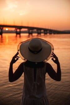 Achteraanzicht van het silhouet van een meisje dat de rand van een strohoed vasthoudt bij de rivier en een stedelijk land...