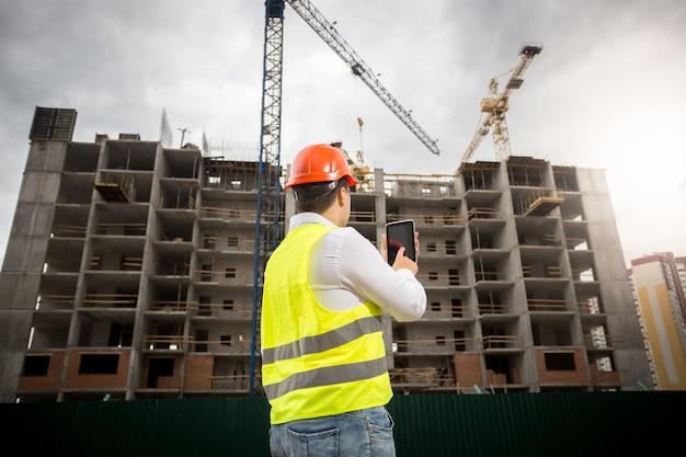 Achteraanzicht van inspecteur die digitale tablet vasthoudt en bouwplaats inspecteert