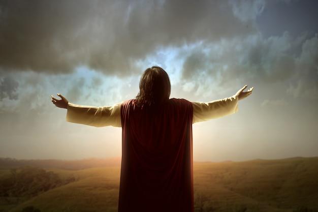 Achteraanzicht van jezus christus opgeheven handen en bidden tot god met een zonsopganghemel