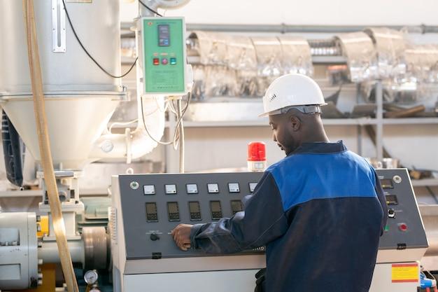 Achteraanzicht van jonge afrikaanse mannelijke werknemer in overall en veiligheidshelm die voor het bedieningspaneel van een enorme industriële machine en draaiknop staat