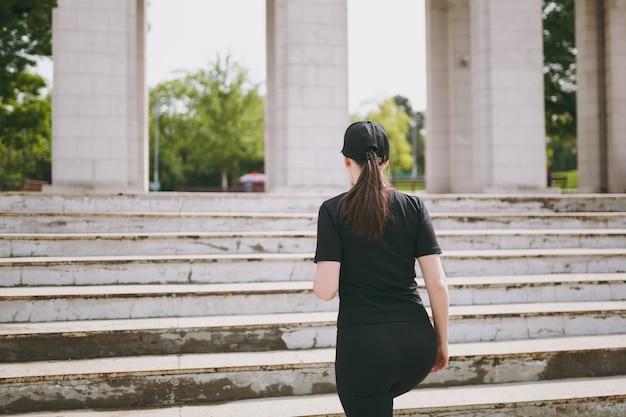Achteraanzicht van jonge atletische sterke brunette vrouw in zwart uniform en pet die sportoefeningen doet, opwarmen voordat ze klimmen op trappen in stadspark buitenshuis