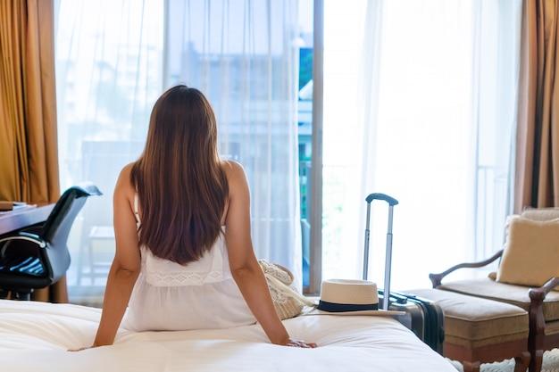 Achteraanzicht van jonge aziatische reiziger in witte jurk ontspannen kijken door een raam in de hotelkamer na aankomst met bagage op de voorgrond.