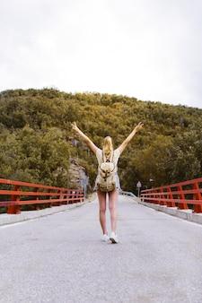 Achteraanzicht van jonge blonde vrouw met rugzak en handen omhoog lopen op de weg over een brug in de buurt van de berg. reizen en avontuur concept. reiziger midden in het bos. alleen reizen