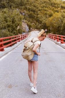 Achteraanzicht van jonge blonde vrouw met rugzak lopen op de weg over een brug in de buurt van de berg. reizen en avontuur concept. reiziger midden in het bos. alleen reizen