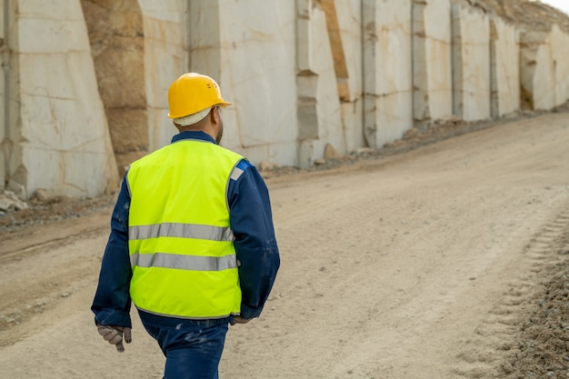 Achteraanzicht van jonge bouwer in werkkleding die langs de muur van een onafgewerkt gebouw beweegt