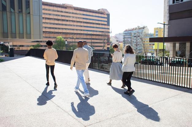 Achteraanzicht van jonge burgers lopen op straat met telefoons