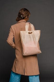 Achteraanzicht van jonge casual vrouw in elegante jas en spijkerbroek met textiel draagtas op schouder