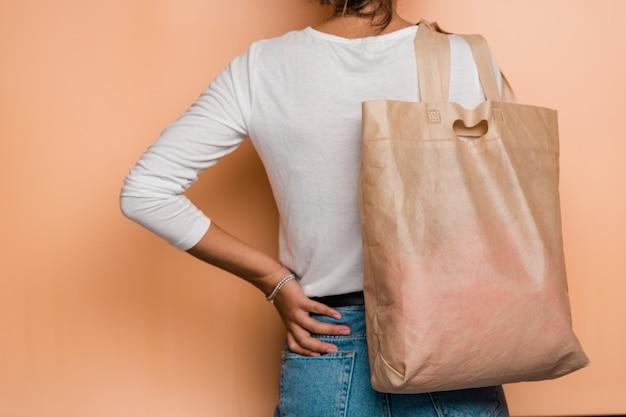 Achteraanzicht van jonge casual vrouw met roze textiel draagtas op schouder terwijl poseren in isolatie