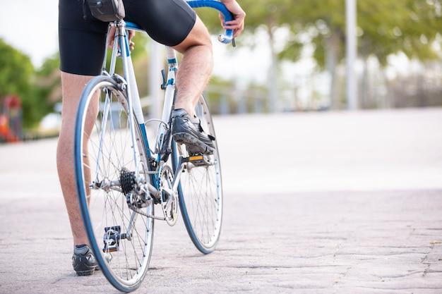 Achteraanzicht van jonge cool mannelijke fietser in sportkleding voorbereiden fietsen in prachtige stadspark