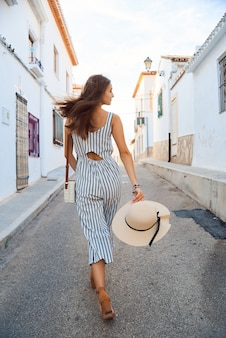 Achteraanzicht van jonge elegante vrouw in stro hoed lopen op de smalle straatjes van de oude stad.