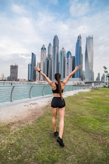 Achteraanzicht van jonge fitness vrouw met opgeheven handen kijken naar wolkenkrabbers. sport succes concept.