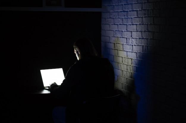 Achteraanzicht van jonge geconcentreerde man met behulp van laptop