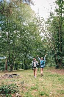 Achteraanzicht van jonge gelukkige wandelaar vrouw die armen opheft en geniet van de natuur met haar vriendin. vrijheid en natuur concept.