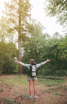 Achteraanzicht van jonge gelukkige wandelaar vrouw met rugzak die haar armen opheft en geniet van het bos. vrijheid en natuur concept.