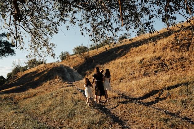 Achteraanzicht van jonge gezin lopen op de weg op de heuvel in zonnige zomerdag