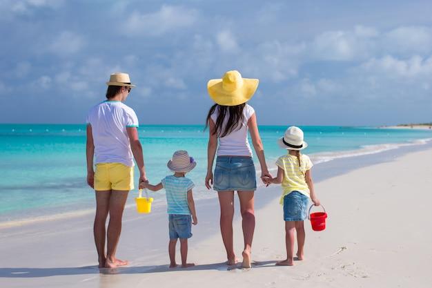 Achteraanzicht van jonge gezin met twee kinderen op caribische vakantie