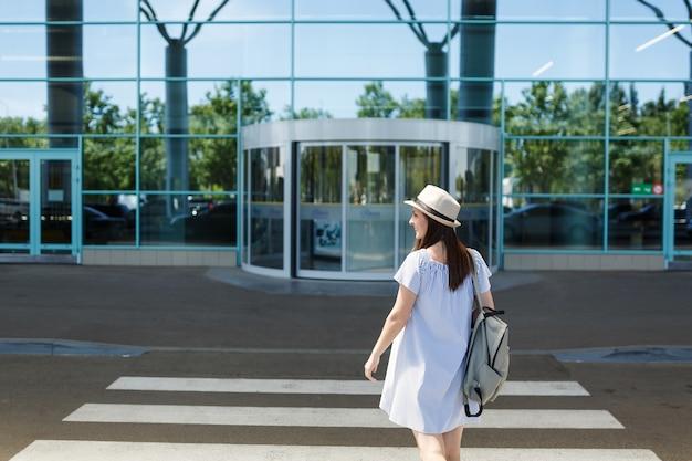 Achteraanzicht van jonge glimlachende reizigerstoeristenvrouw in hoed met rugzak die op zebrapad staat op de internationale luchthaven