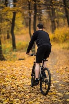 Achteraanzicht van jonge knappe man met een fiets op bosweg tussen bomen in zonsondergang. sport en een gezonde levensstijl. reis naar regenwoud