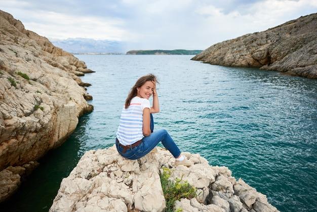 Achteraanzicht van jonge lachende vrouw zit alleen op steenachtige kust van zee, genieten van prachtig uitzicht