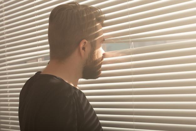 Achteraanzicht van jonge man met baard gluurt door gat in de jaloezieën