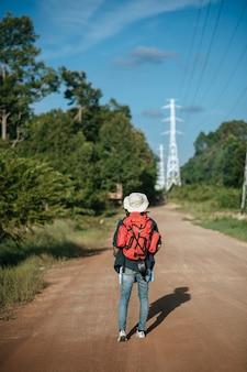 Achteraanzicht van jonge man reiziger met rugzak die sombrero draagt en papieren kaart in de hand houdt, hij loopt en kijkt vooruit, heeft een hoogspanningspaal en de overwoekerde struiken naast op straat