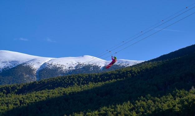 Achteraanzicht van jonge man rijden op zip line tegen blauwe hemel