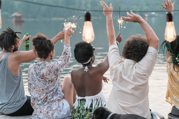 Achteraanzicht van jonge mensen die de vakantie vieren met drankjes en wonderkaarsen buitenshuis
