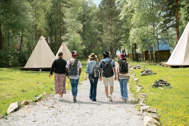 Achteraanzicht van jonge mensen met boekentassen die op de camping aankwamen en langs het pad op de festivalcamping liepen